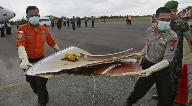 Members of the Indonesian Search and Rescue Agency carry pieces from AirAsia Flight 8501 (AP)