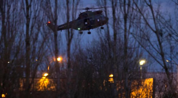 A helicopter flies over the building where the suspects in the Charlie Hebdo massacre were holed up (AP)