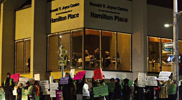 Protesters demonstrate before the performance by Bill Cosby in Hamilton (AP/The Canadian Press)