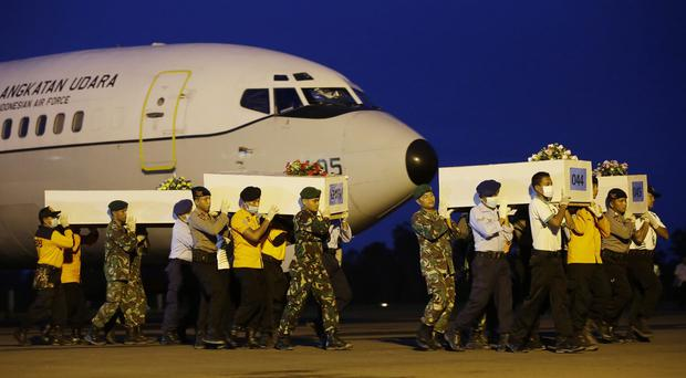 National Search and Rescue Agency members carry coffins containing bodies of the AirAsia victims at the airport in Pangkalan Bun (AP)