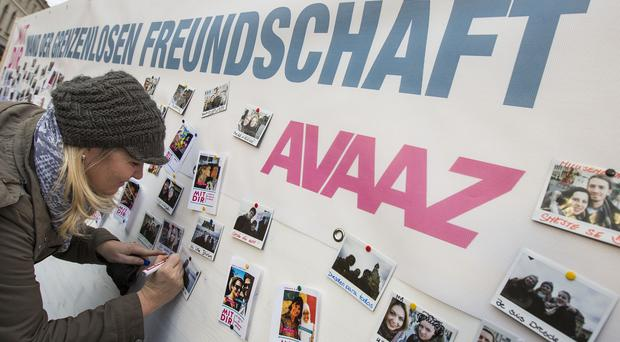 People are adding their names to a giant wall of messages expressing hope and unity during a massive anti-Pegida gathering in Dresden (AP/AVAAZ)
