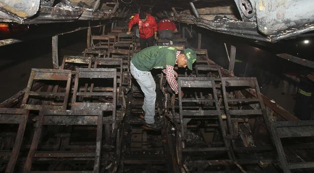 Rescue workers search through the wreckage of the passenger bus (AP)