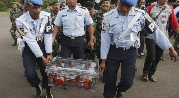 Indonesian air force staff carry the flight data recorder of the ill-fated AirAsia Flight 8501 (AP)