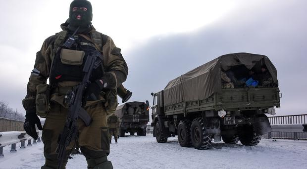 A pro-Russian rebel guards the road near the airport of Donetsk. (AP)