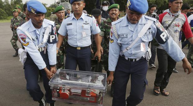 Indonesian air force personnel carry the flight data recorder of ill-fated AirAsia Flight 8501. (AP)