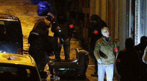Specialist officers examine a street in Verviers after security forces killed two people and arrested one in an anti-terror raid (AP)