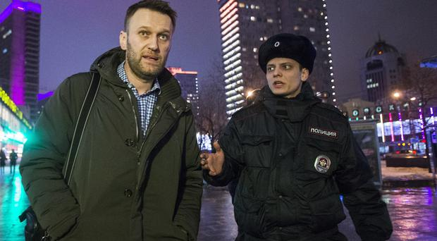 Alexei Navalny, left, was detained by police after defying his house arrest on Wednesday. (AP)
