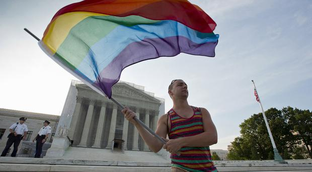 Gay rights advocate Vin Testa waves a rainbow flag in front of the US Supreme Court in Washington (AP)