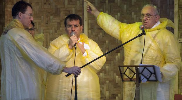 Pope Francis dons a plastic mac to address the faithful in stormy Tacloban (AP)