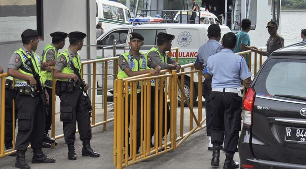 Armed police and security staff stand guard as a ferry carrying ambulances sets off for the execution site (AP)