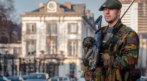 A Belgian para-commando patrols near the prime minister's office in Brussels (AP)