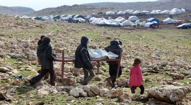 Iraqis from the Yazidi minority carry a bed frame on Mount Sinjar in northern Iraq, as IS released 200 captive Yazidis (AP)