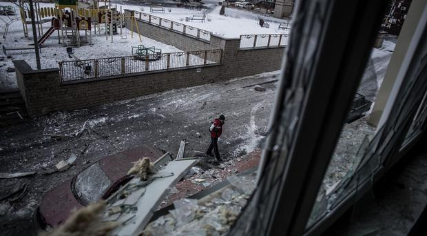 A Ukrainian man walks through the debris after the centre of Donetsk was shaken by artillery fire as a bitter battle raged for control over the city's airport (AP)