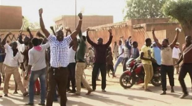Protesters chant and raise their arms during protests in Niamey, Niger (AP)
