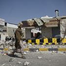 A Houthi Shiite Yemeni walks past a building damaged during recent clashes near the presidential palace in Sanaa (AP)