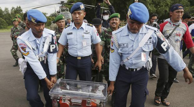 Indonesian air force personnel carry the flight data recorder of the ill-fated AirAsia Flight 8501 that crashed in the Java Sea (AP)