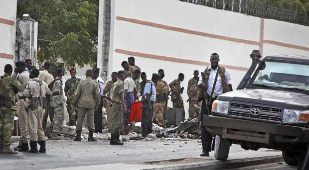 Somali soldiers gather near the destroyed gate of the SYL hotel following a suicide car bomb attack in Mogadishu (AP)