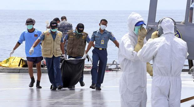 Crew members carry the remains of a victim of the AirAsia Flight 8501 to a waiting helicopter