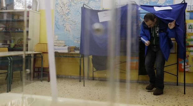 A man casts his vote at a polling station in Athens (AP)