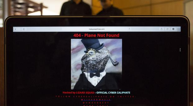 Workers stand behind a computer showing the hacked Malaysia Airlines website, at a Kuala Lumpur cafe (AP)