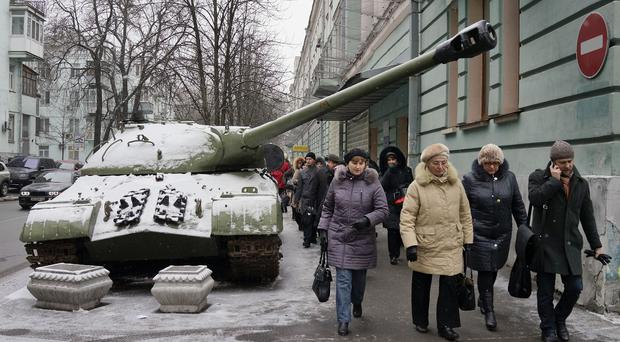 People pass by a tank in Kiev that has been used by pro-Russian separatists in the country's east and then brought to the Ukrainian capital as a symbol of the current conflict. (AP)
