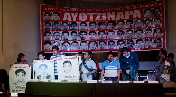 Parents of missing students with a banner carrying the photos of all 43. (AP)
