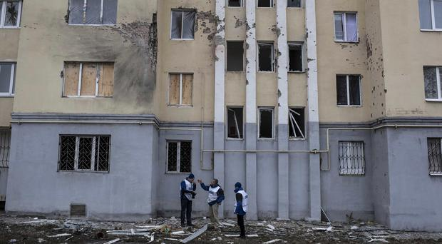 International monitors investigate an apartment building damaged in shelling in Mariupol. (AP)