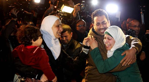 A man comforts the wife of Jordanian pilot Lt Muath al-Kaseasbeh during a protest in front of the Royal Palace in Amman (AP)
