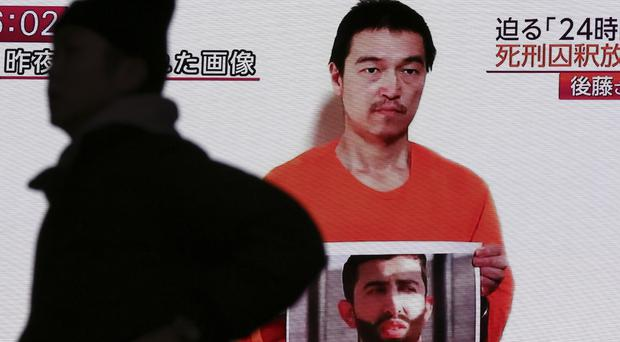 In Tokyo a screen shows TV news reports of a YouTube video of Japanese hostage Kenji Goto (AP)