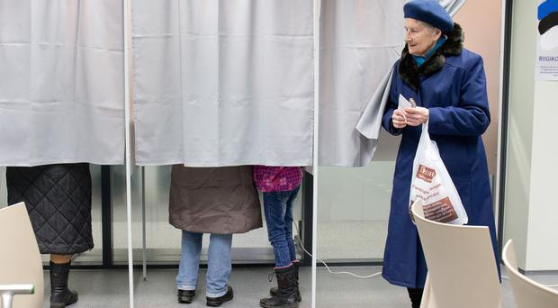 A woman leaves a polling booth in Tallinn (AP)