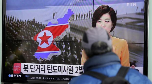 A North Korean TV news programme announcing the firing of the missiles is watched at Seoul railway station (AP)