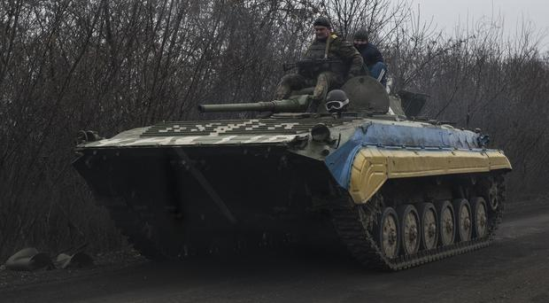 Ukrainian servicemen ride atop an armoured vehicle near Artemivsk, eastern Ukraine (AP)
