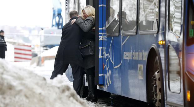 Bombing survivor Heather Abbott is helped from a bus outside court in Boston. (AP)