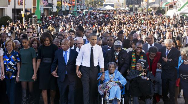 President Barack Obama walks across the bridge hand-in-hand with Amelia Boynton, who was beaten during Bloody Sunday 50 years ago (AP)
