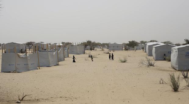 Nigerians who fled Boko Haram to Chad walk through the Baga Sola refugee camp near the shore of Lake Chad (AP)