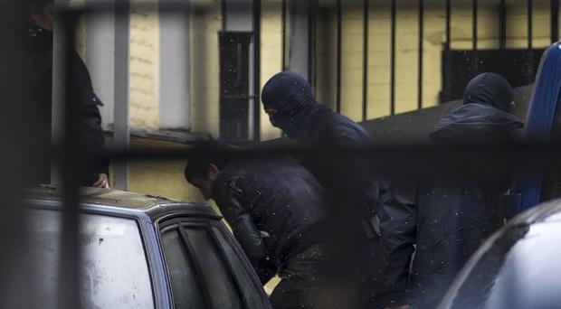 Police escort the suspects in the killing of Boris Nemtsov into a court in Moscow