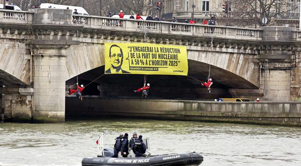 Greenpeace activists dangle a banner from a bridge over the Seine in central Paris (AP)