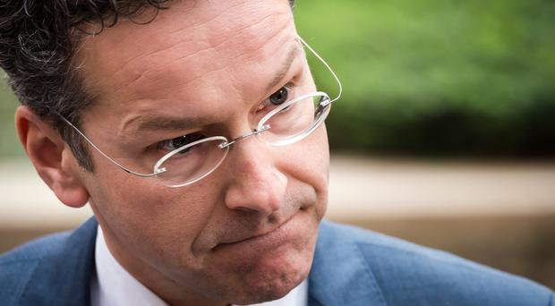Jeroen Dijsselbloem talks with journalists as he arrives for a meeting of Eurogroup finance ministers in Brussels (AP)