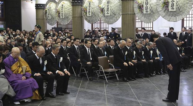 Japanese prime minister Shinzo Abe bows during a Second World War firebombing commemorative service at Tokyo Memorial Hall (AP)