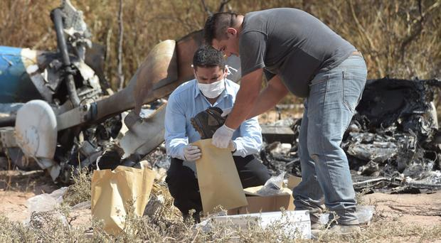 Men remove victims' personal items from the wreckage of the two helicopters yesterday