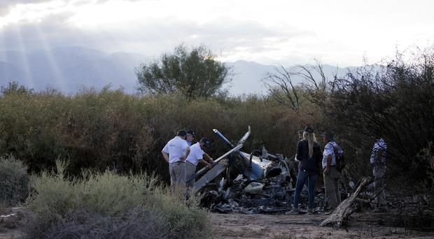 Civil aviation accident investigators inspect the wreckage of one of two helicopters that collided near Villa Castelli, Argentina (AP)