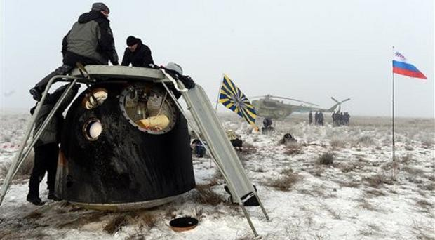Russia's space agency staff check the Soyuz TMA-14M capsule shortly after the landing in a remote area in Kazakhstan (AP)