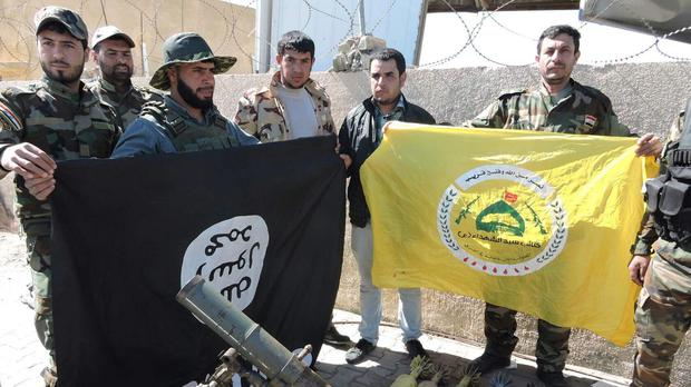 Shiite militiamen pose for a photo with their banner, right, and a captured Islamic State group flag, left, upside down, in Tikrit (AP)