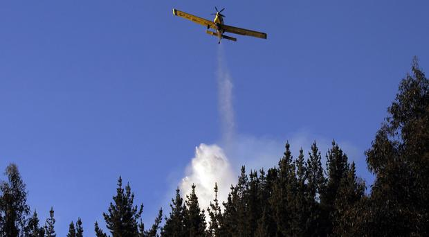 A fire fighting plane dumps water on a forest fire in Valparaiso, Chile (AP)