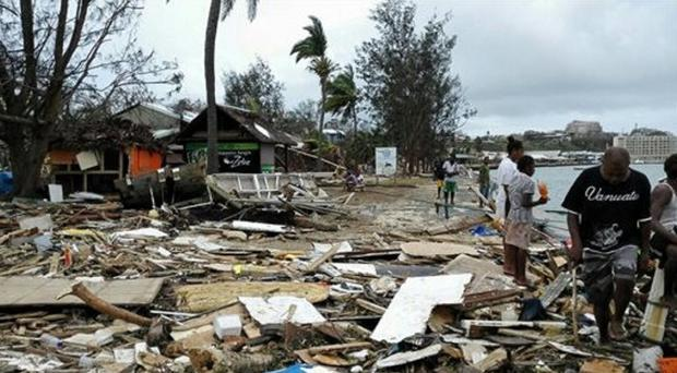 Locals walk past debris in Port Vila, Vanuatu, after Cyclone Pam ripped through the tiny South Pacific archipelago (AP/Xinhua, Luo Xiangfeng)