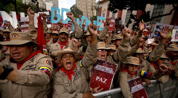 Bolivarian Militia members shout slogans against US president Barak Obama during a pro-government rally outside Miraflores presidential palace in Caracas, Venezuela (AP)