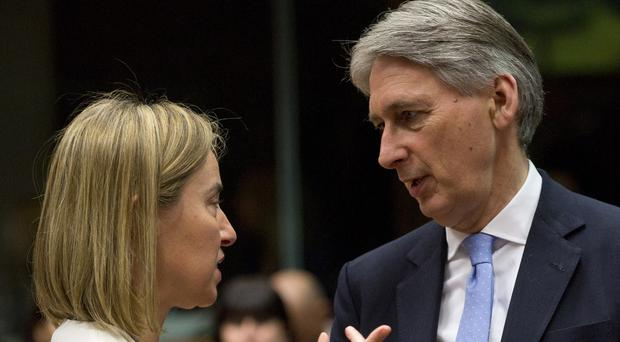 EU High Representative Federica Mogherini speaks with British Foreign Minister Philip Hammond during a meeting in Brussels. (AP)