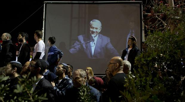 Supporters of Israeli Prime Minister Benjamin Netanyahu, seen on the screen, gather during his election rally in Tel Aviv. (AP)