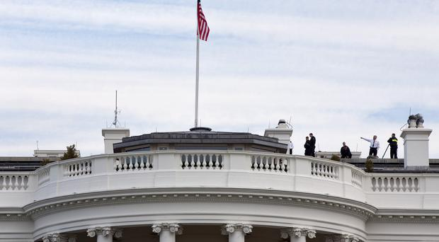 Secret Service agents patrol the top of the White House as seen from the South Lawn (AP)