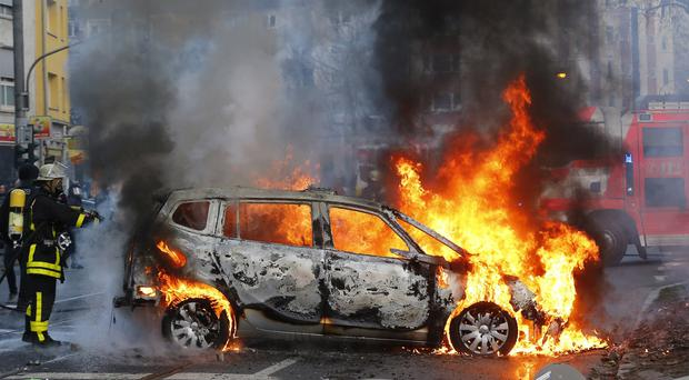 A firefighter extinguishes the flames of a burning police car after clashes between demonstrators and police in Frankfurt (AP)
